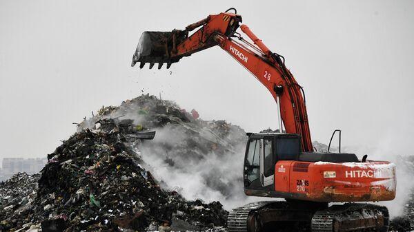 Экскаватор на полигоне твердых бытовых отходов Кучино в Балашихе Московской области