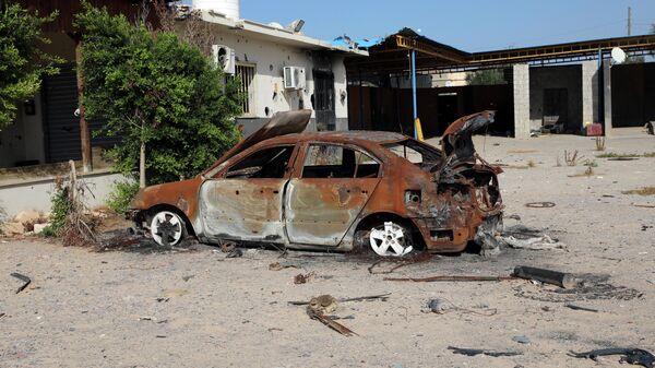Сгоревший в результате вооруженных столкновений автомобиль в Триполи, Ливия. 14 октября 2019