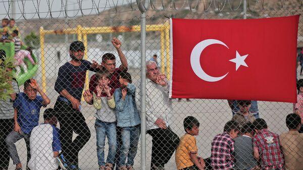 Мигранты стоят за забором в лагере беженцев Низип в провинции Газиантеп, на юго-востоке Турции