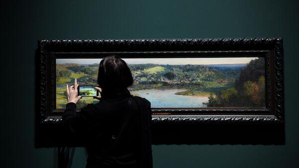 Посетительница фотографирует картину Василия Поленова Вид на Тарусу в Третьяковской галерее на Крымском валу
