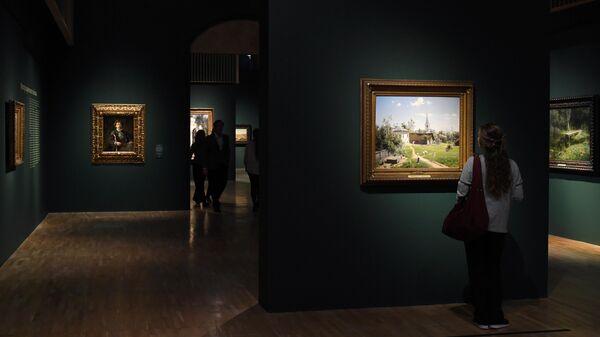 Посетительница рассматривает картину Василия Поленова Московский дворик (1878 г.) в Третьяковской галерее на Крымском валу