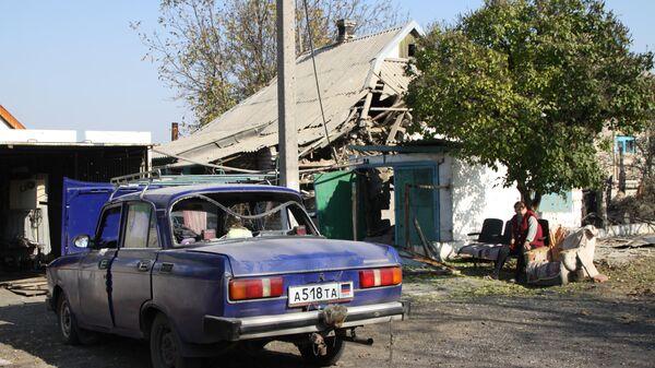 Поврежденный автомобиль у жилого дома в поселке Старомихайловка города Донецка после обстрела