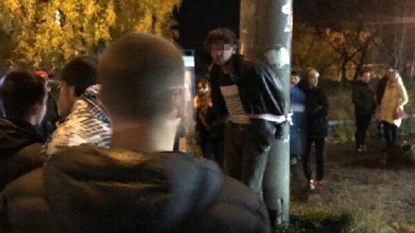 Мужчина, привязанный к столбу, в окружении десятков местных жителей. Цигломень