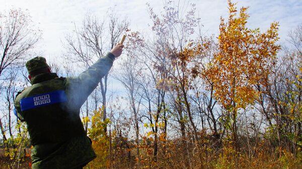 Представитель народной милиции ЛНР запускает белую сигнальную ракету в поселке Золотое