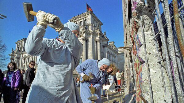 Жители ГДР разбирают Берлинскую стену на сувениры.