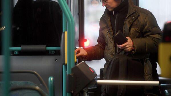 Пассажир прикладывает билет к валидатору в автобусе