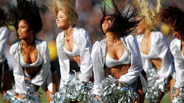 Девушки из группы поддержки американского футбольного клуба Окленд Рэйдерс выступают во время матча между Окленд Рэйдерс и Детройт Лайонс