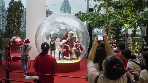 Семья в костюмах Санта-Клауса позирует внутри рождественского украшения в торговом центре в Бангкоке