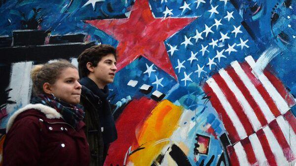 Молодые люди у фрагмента Берлинской стены на Мюленштрассе