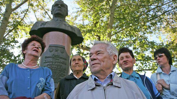 Михаил Калашников на родине в селе Курья Алтайского края с односельчанами на фоне своего бюста