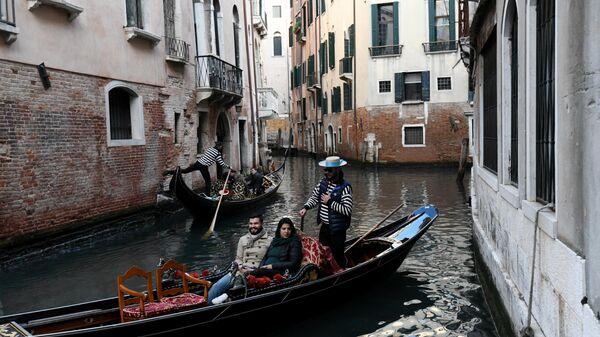 Гондолы с туристами на канале в Венеции