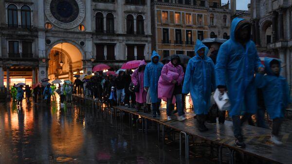 Туристы на площади Сан-Марко во время наводнения в Венеции