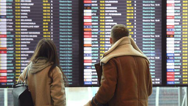 Пассажиры смотрят информационное табло в аэропорту