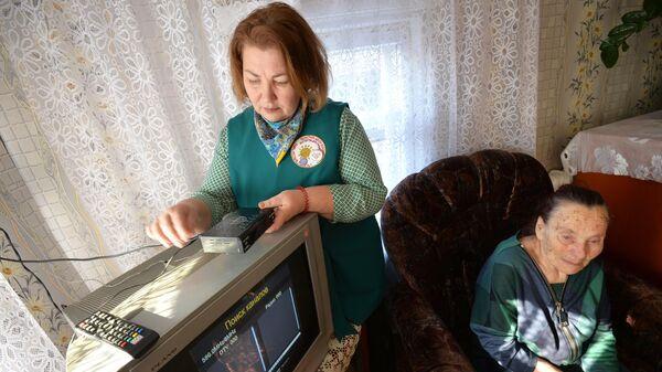 Волонтер помогает ветерану Великой Отечественной войны настроить прием цифрового телевидения