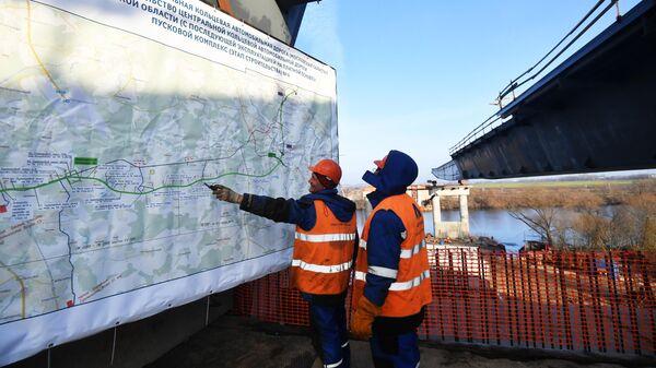 Рабочие осматривают план строительства четвертого пускового комплекса Центральной кольцевой автомобильной дороги в Москве