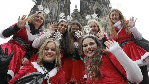 Девушки в новогодних костюмах позируют перед Кельнским собором