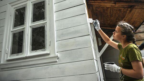 Девушка волонтер красит стены