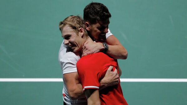 Tennis - Davis Cup Finals - Caja Magica, Madrid, Spain - November 18, 2019   Canada's Denis Shapovalov is embraced by captain Frank Dancevic as he celebrates after winning his group stage match against Italy's Matteo Berrettini   REUTERS/Susana Vera