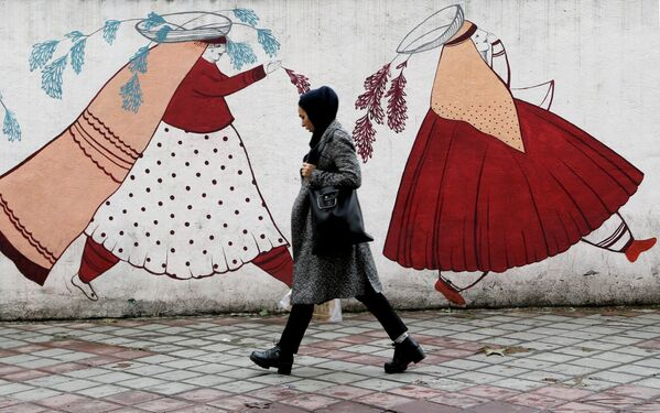 Женщина проходит мимо расписанной стены в Тегеране, Иран