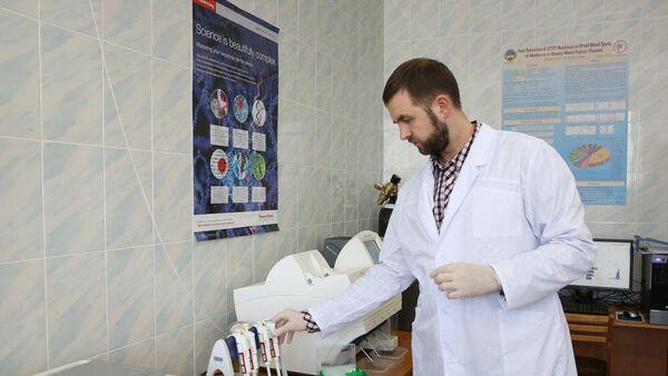 Научный сотрудник НОЦ Медицинского института СурГУ Максим Донников загружает подготовленную библиотеку образцов генетического материала на борт секвенатора нового поколения (NGS)