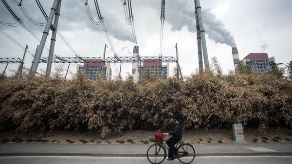 Мужчина проезжает мимо угольной электростанции Shanghai Waigaoqiao Power Generator Company в Шанхае, Китай