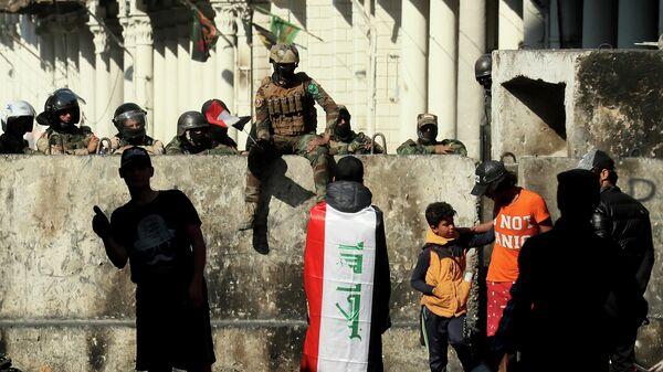 Сотрудники правоохранительных органов и демонстранты во время акции протеста в Багдаде. 30 ноября 2019