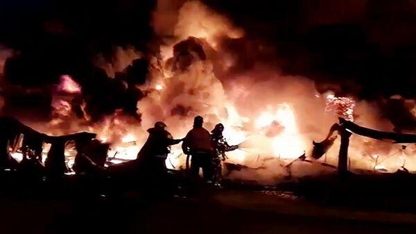 Сотрудники противопожарной службы МЧС России тушат пожар в ангаре на территории промышленной зоны в Санкт-Петербурге. Стоп-кадр с видео, предоставленного МЧС