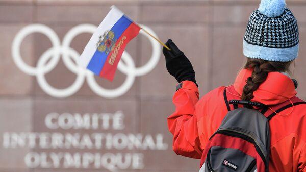Болельщица с российским флагом на фоне штаб-квартиры Международного олимпийского комитета (МОК) в Лозанне (Швейцария)