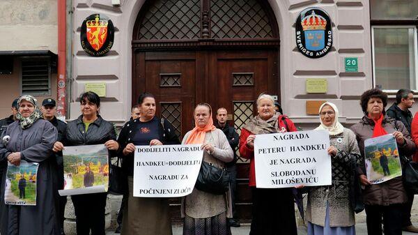 Боснийские женщины, родственники которых погибли во время резни в Сребренице, протестуют у здания шведского посольства в Сараево, Босния и Герцеговина