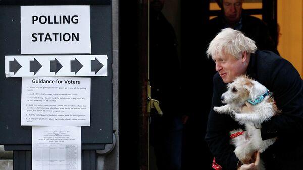 Премьер-министр Великобритании Борис Джонсон со своей собакой по кличке Дилэн на избирательном участке в Лондоне
