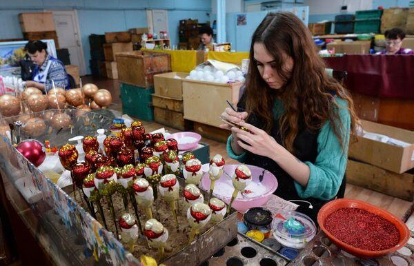 Женщины вручную расписывают елочные игрушки на фабрике Бирюсинка в Красноярске