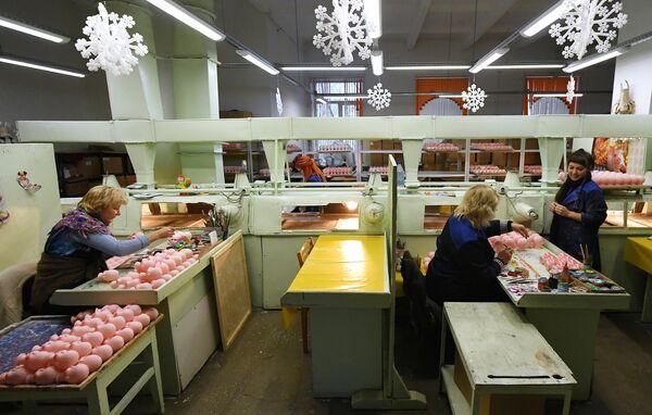 Художницы раскрашивают вручную головы кукол Деда Мороза, сделанные по классическим технологиям из поливинилхлорида, на фабрике Бирюсинка в Красноярске