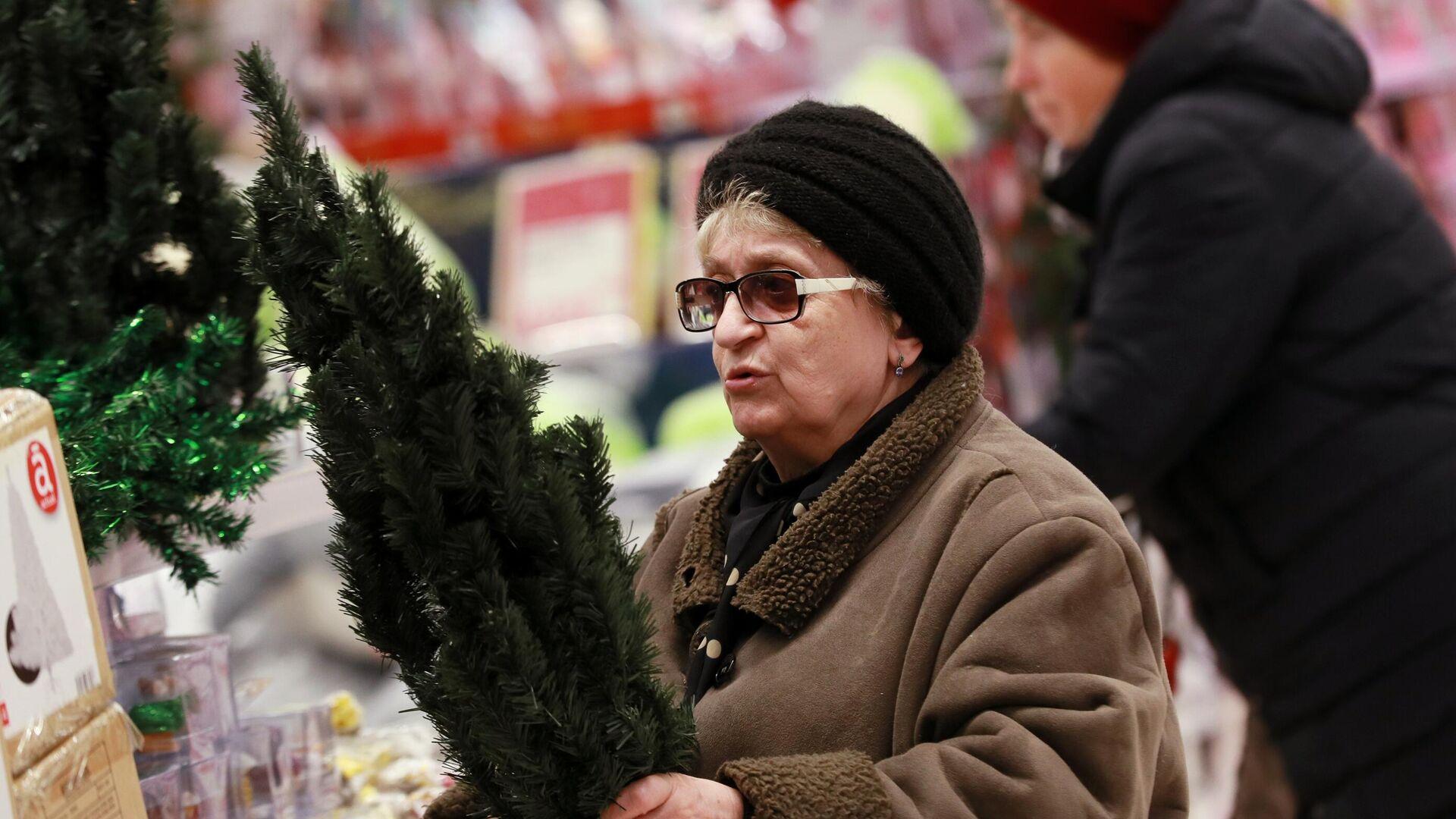 Женщина выбирает новогоднюю ёлку в гипермаркете Ашан в Москве - РИА Новости, 1920, 01.12.2020