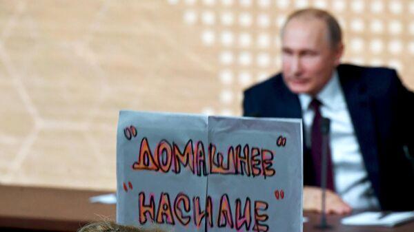 Журналист с плакатом Домашнее насилие во время большой ежегодной пресс-конференции президента РФ Владимира Путина