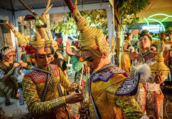 Танцоры готовятся выступить на уличном фестивале в Бангкоке