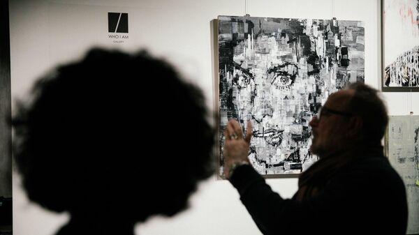 Посетители на фоне работ Игната Кравцова на выставке Faces в галерее Who I Am
