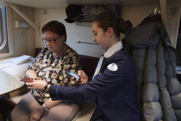 Проводница проверяет билет у пассажирки в поезде Таврия, следующем по маршруту Санкт-Петербург - Севастополь