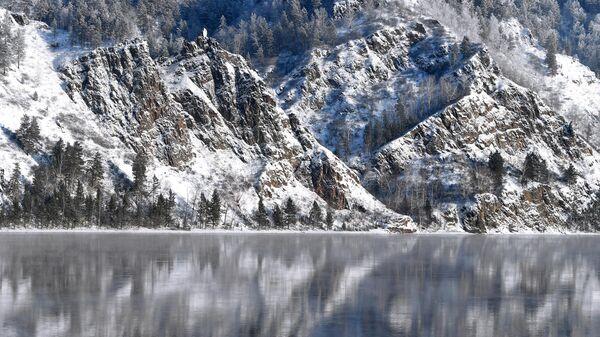 Покрытый снегом крутой таежный берег реки Енисей напротив города Дивногорска Красноярского края