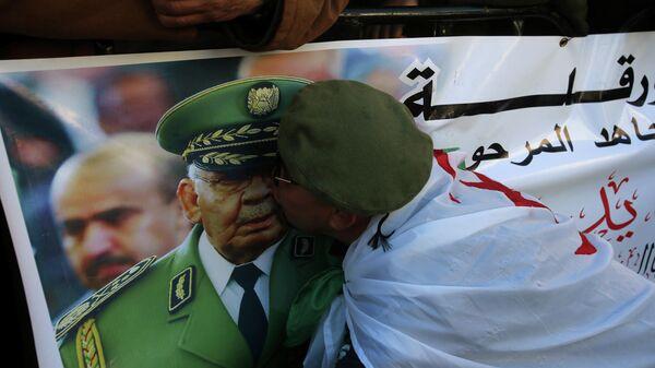 Женщина целует изображение генерал-лейтенанта Ахмеда Гаеда Салаха во время его похорон в Алжире