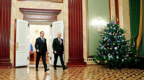 Президент РФ Владимир Путин и председатель правительства РФ Дмитрий Медведев на предновогодней встрече с членами правительства РФ