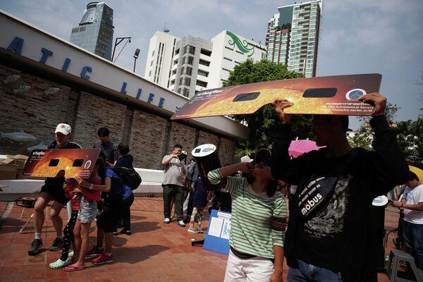 Люди наблюдают частичное солнечное затмение в Научном Центре образования в Бангкоке, Таиланд. 26 декабря 2019 года