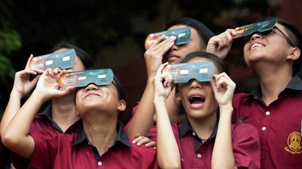 Студенты  смотрят солнечное затмение в школе Santiratwitthayalai в Бангкоке, Таиланд. 26 декабря 2019 года