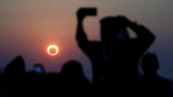 Люди наблюдают за кольцевым солнечным затмением на Джабаль-Арбе в Хофуфе, в восточной провинции Саудовской Аравии