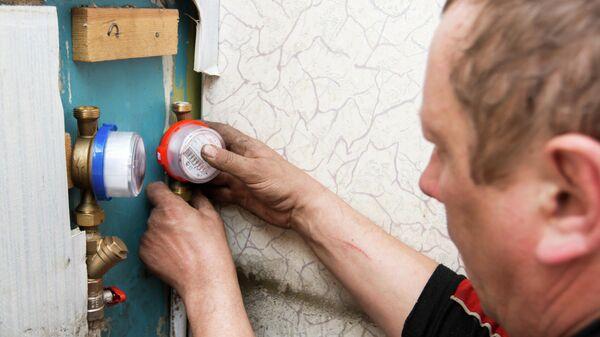 Сантехник осуществляет установку прибора индивидуального учета водопотребления в квартире жилого дома