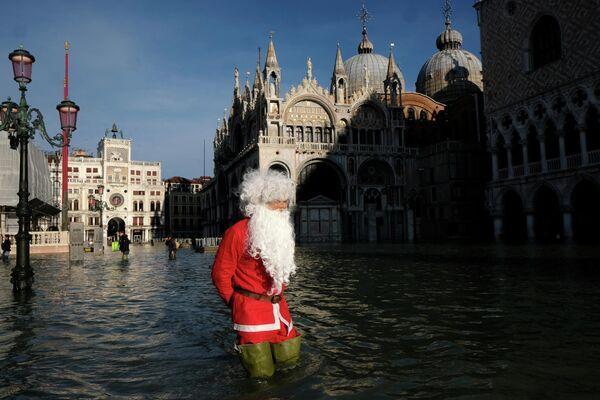 Мужчина в костюме Санта-Клауса на площади Святого Марка во время наводнения в Венеции