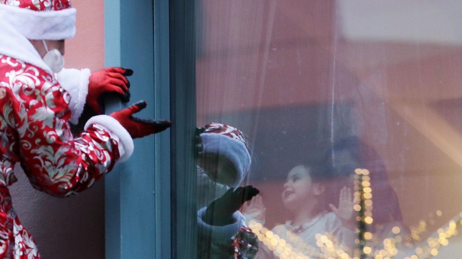 Сотрудник департамента по делам гражданской обороны, чрезвычайным ситуациям и пожарной безопасности города Москвы в костюме Деда Мороза поздравляет пациентов Морозовской детской больницы - РИА Новости, 1920, 11.11.2020