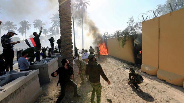 Протестующие подожгли стену посольства США в  Багдаде в знак осуждения авиаударов США в Ираке. 31 декабря 2019