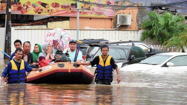 Спасатели  эвакуируют местных жителей  во время наводнения после сильного дождя  недалеко от Джакарты, Индонезия. 1 января 2020