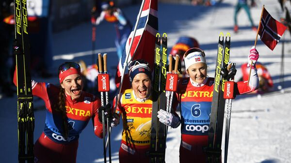 Слева направо: Наталья Непряева (Россия), занявшая второе место, Тереза Йохауг (Норвегия), занявшая первое место, Ингвильд Остберг (Норвегия), занявшая третье место в общем зачете на соревнованиях по лыжным гонкам Тур де Ски в итальянском Валь-ди-Фьемме.
