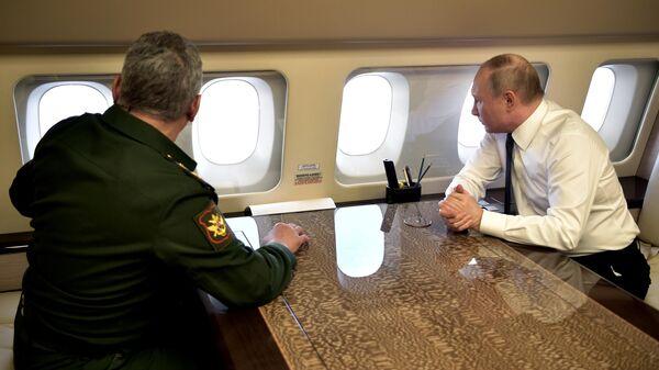 Президент РФ Владимир Путин и министр обороны РФ Сергей Шойгу на борту президентского самолета во время полета в Сирию